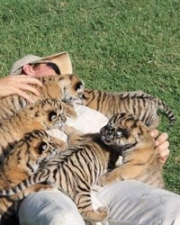 Joe Exotic playing with baby tigers